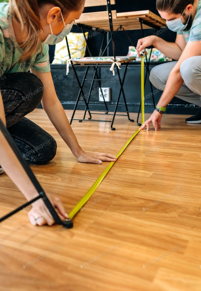 Workers measuring social distance on the floor