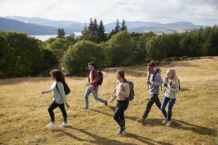 A group of five young adult friends smile while walking on a rural path
