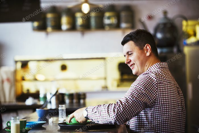 Specialist coffee shop. A man seated at a counter with a cup of coffee.
