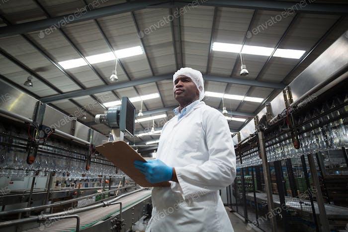 Werksingenieur pflegt Rekord auf Zwischenablage in der Fabrik