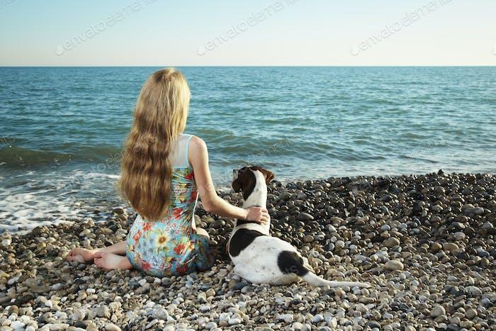 Schöne Frau mit einem Hund am Strand