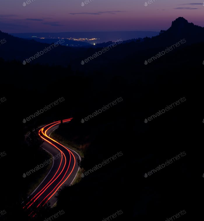car moving fast on a winding road  at dusk