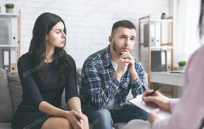 Serious man talking to psychiatrist during marital therapy session