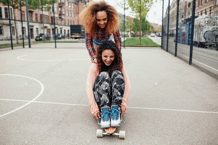 Young women skating in a basketball court