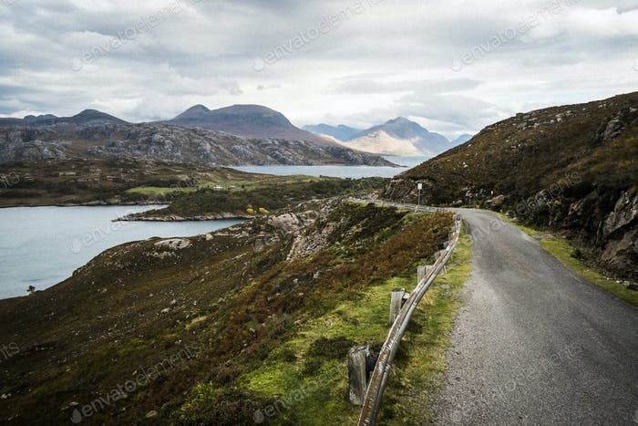 Landscape with rural road cutting through mountains and lochs under a cloudy sky.