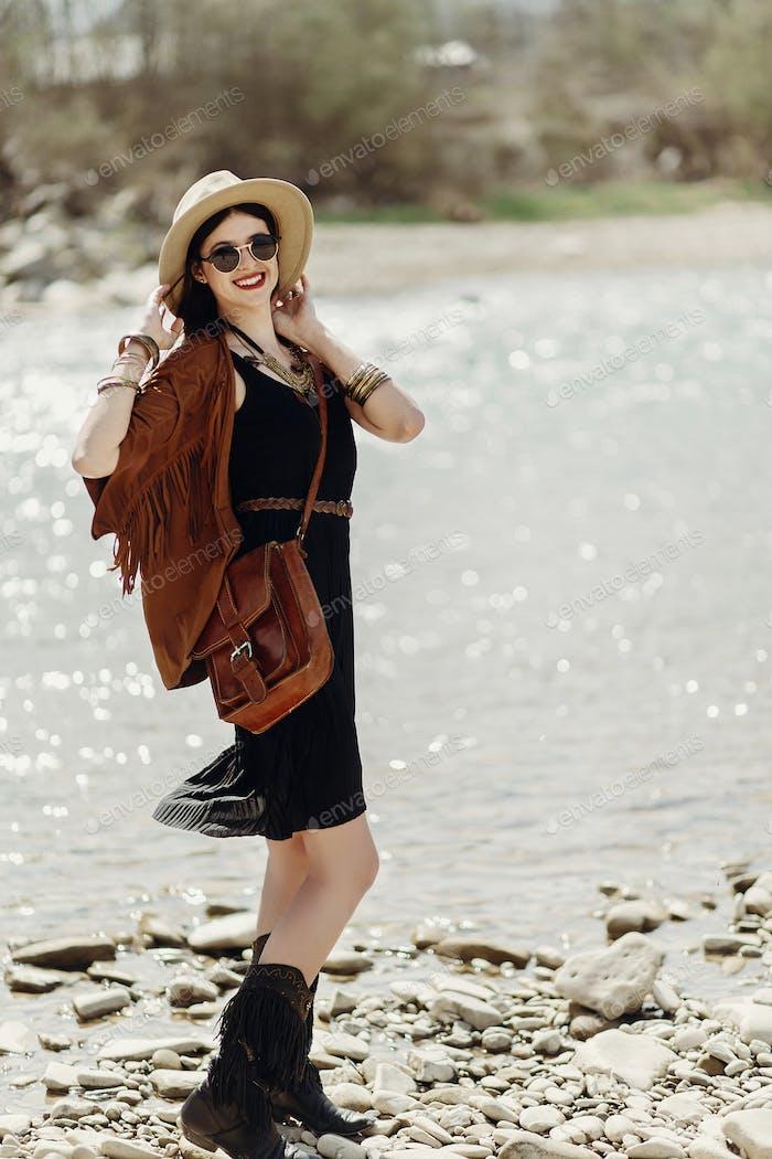 stilvolle Hipster Frau posiert in Hut mit windigem Haar, in Fransen Poncho und Accessoire
