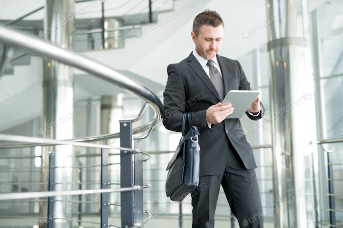 Modern businessman in office hall of large company