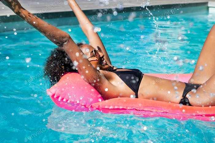 Happy african woman splashing water in pool