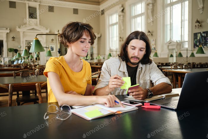Two young casual students dreamily making notes studying together in library of university