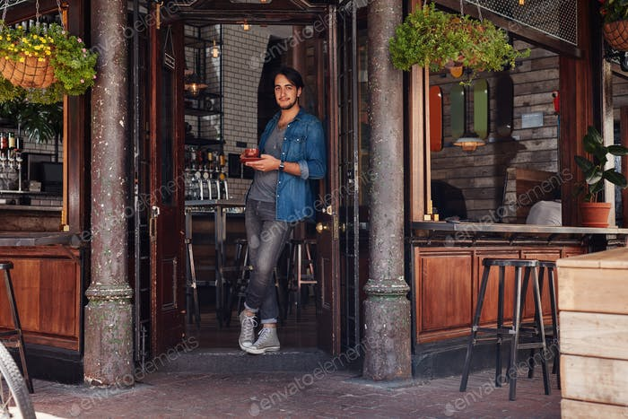 Stylish young man at a cafe entrance