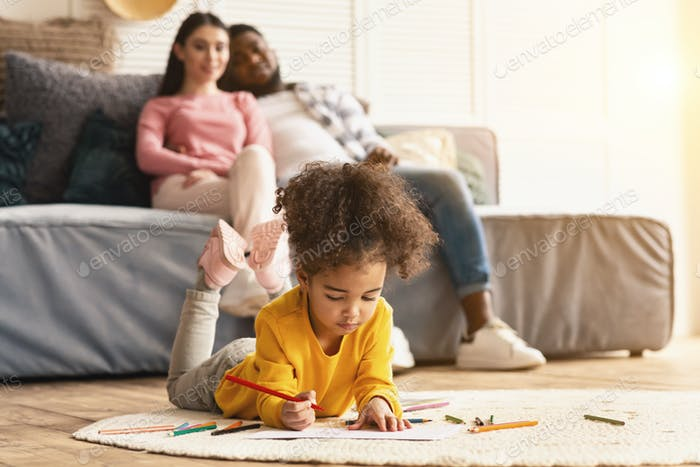 Child draws on the floor, parents sitting on couch