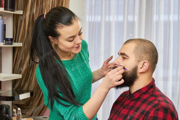 Makeup artist is applying foundation