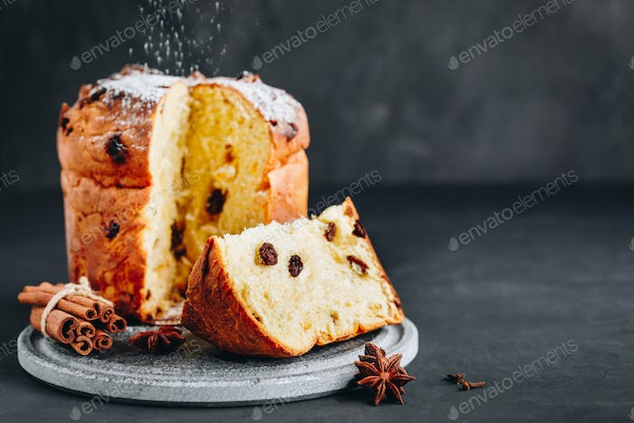 Traditional Christmas Panettone cake with dried fruits on dark stone background