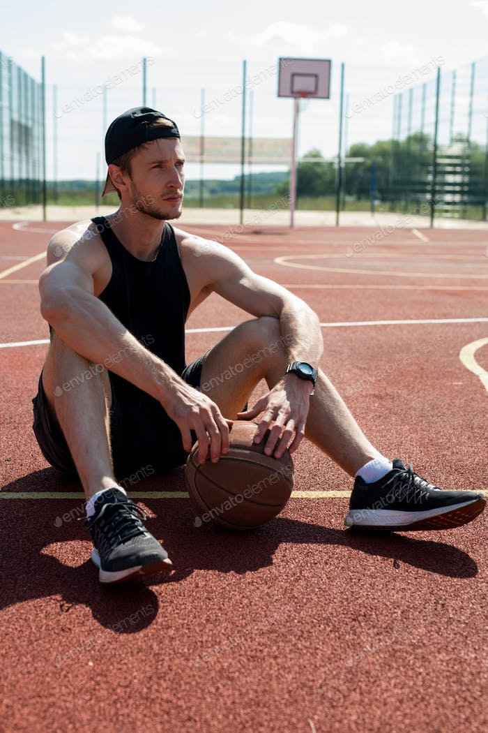 Young Man Resting in Basketball Court