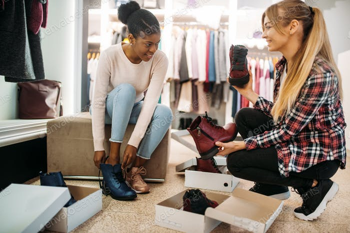 Two female friends trying on shoes, shopping