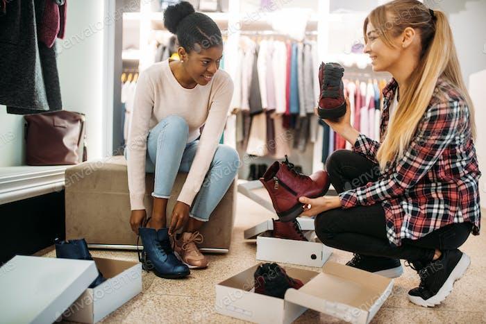 Zwei weibliche Freunde versuchen auf Schuhe, Einkaufen