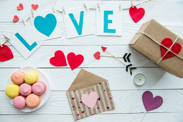 Top view of Valentines day decorations, macaroon cookies and gift box on wooden table