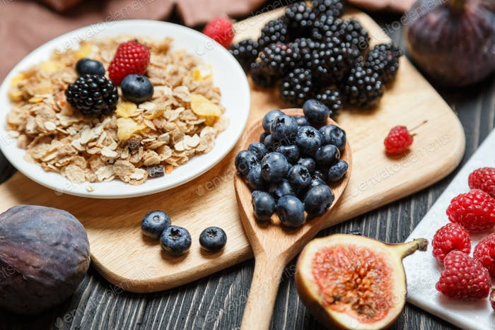 Healthy breakfast set. Muesli and berries on dark rustic background