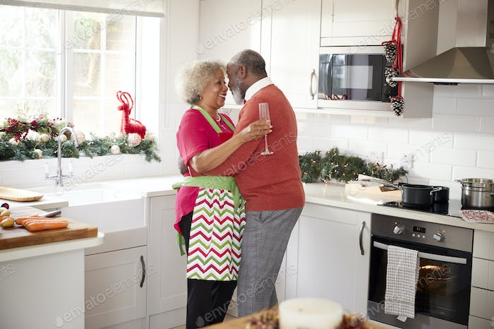 Happy mature black couple holding champagne glasses on Christmas Morning, embracing