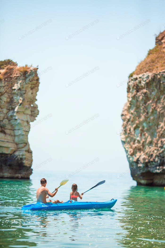 Sporty attractive family kayaking on sea together