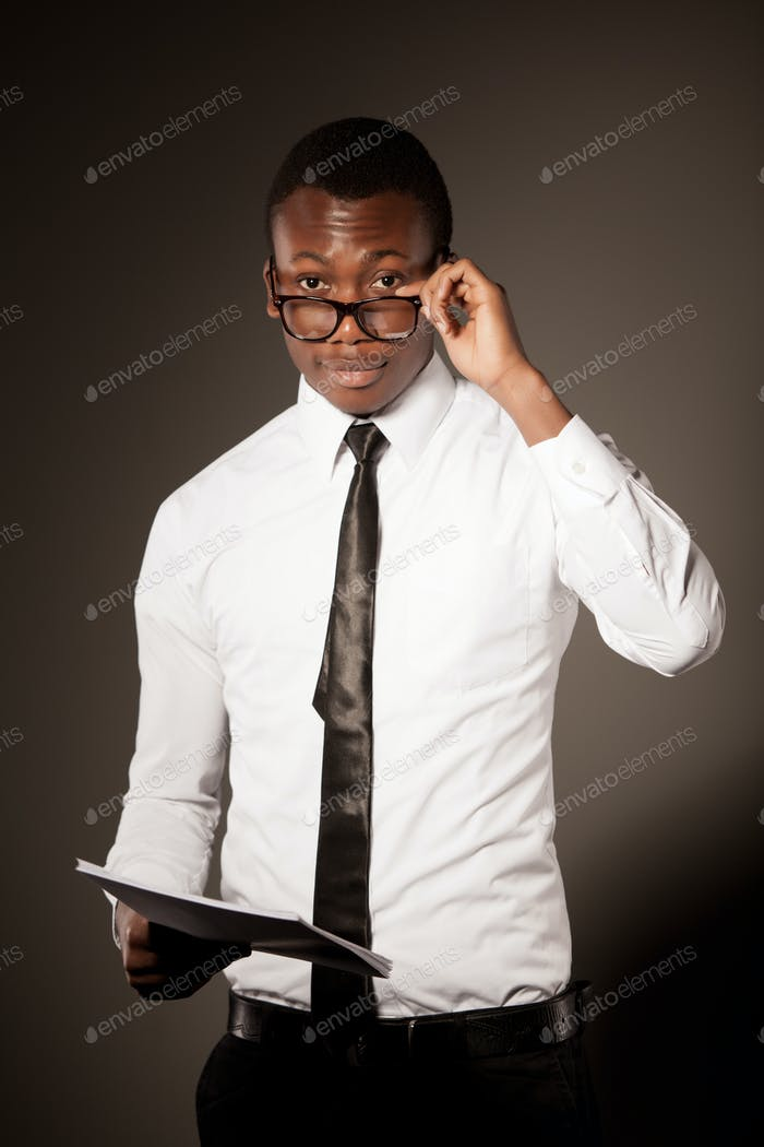 Young positive handsome african businessman in stylish shirt, tie and glasses standing with
