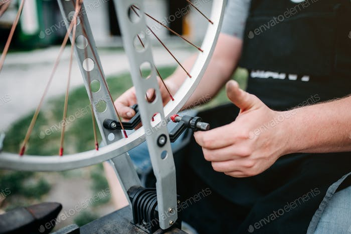 Male person adjusts bike spokes and wheel