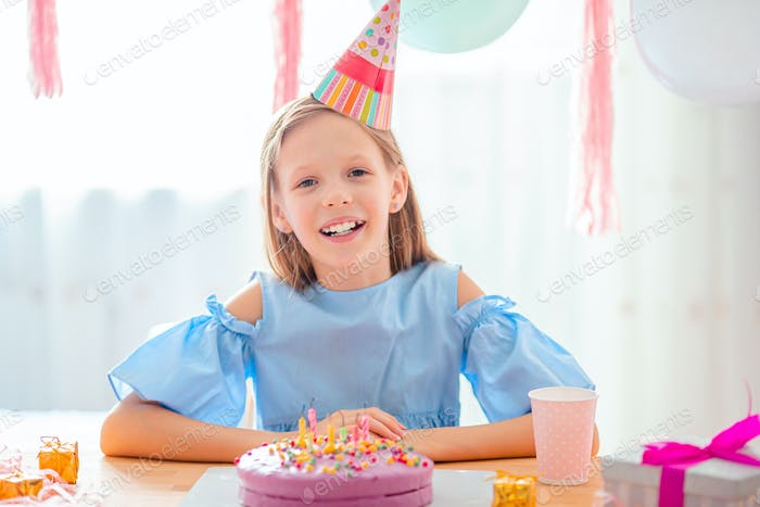 Caucasian girl is dreamily smiling and looking at birthday rainbow cake. Festive colorful background