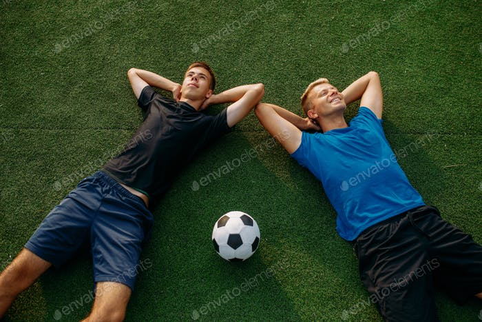 Two male soccer players lying on the grass