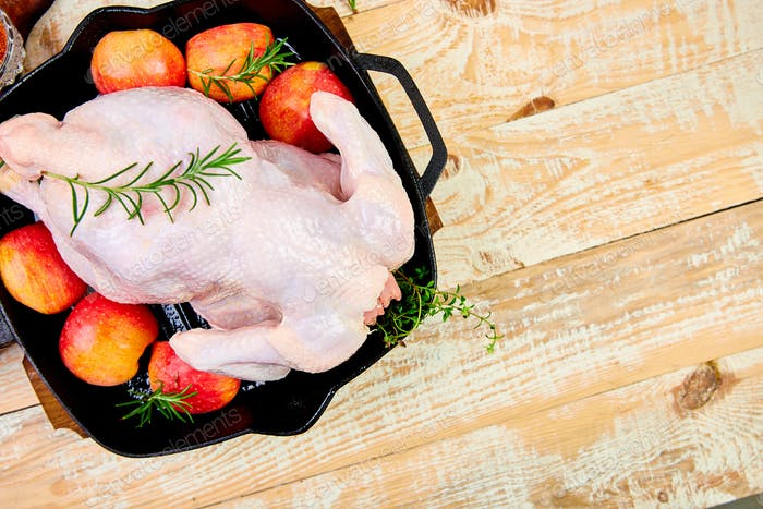 Whole raw chicken in skillet  or iron pan Ready to cook.