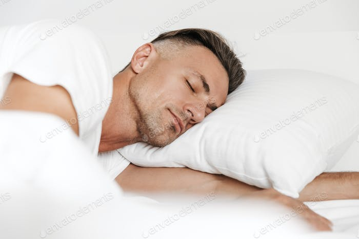 Handsome man sleeping in bed