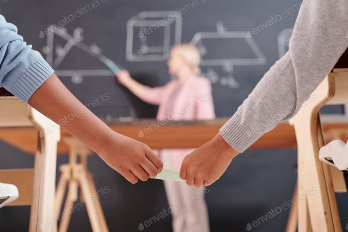 Hands of two schoolkids passing each other small notepaper with right answer