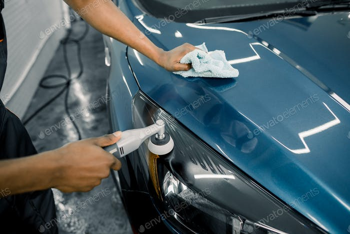 Detailing and polishing of car headlight on car. Hands of dark skinned worker with orbital polisher