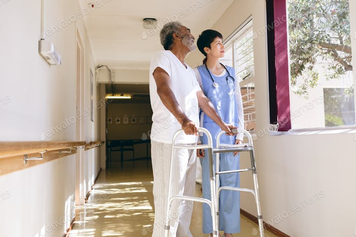 Female nurse and senior male patient interacting with each other in the retirement home