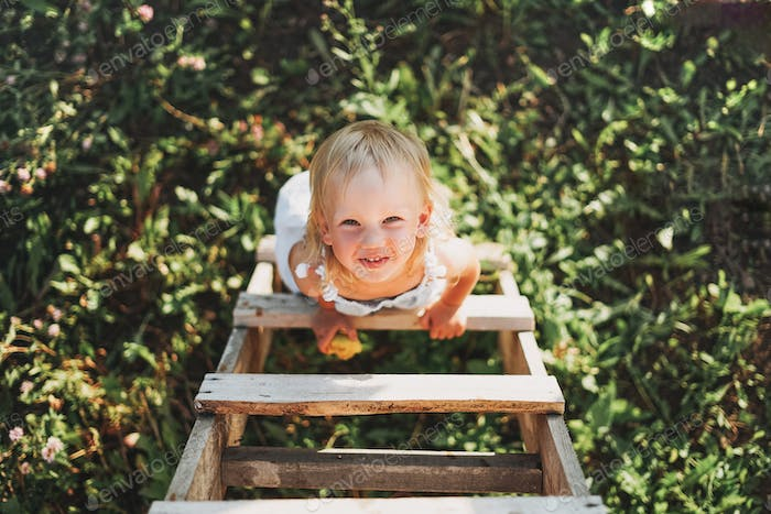 Cute toddler little girl climbs up the ladder