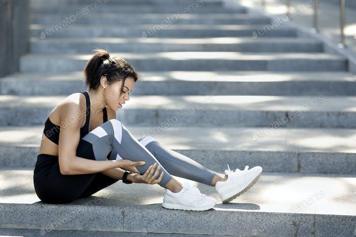 Afrikanische Frau in Sportkleidung sitzt auf der Treppe, massieren Ancle