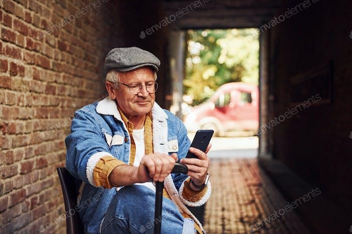 Stilvolle Senior in modischer Kleidung und in Brille sitzt auf dem Stuhl und verwendet Telefon