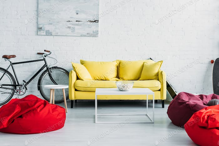 spacious furnished living room with cozy beanbag chairs and comfortable yellow sofa