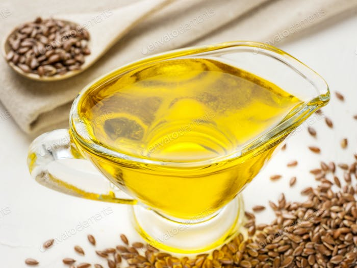 Brown flax seeds in spoon and flaxseed oil