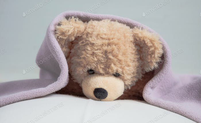 Cute teddy laying on bed mattress covered with a towel
