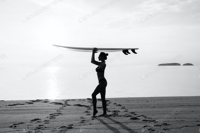 black and white silhouette of fit girl on the beach
