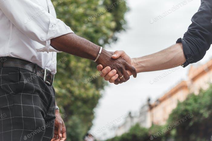 Handshake between african and a caucasian man outdoors