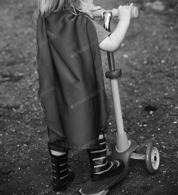 Superhero Baby Boy mit Scooter Adorable Konzept