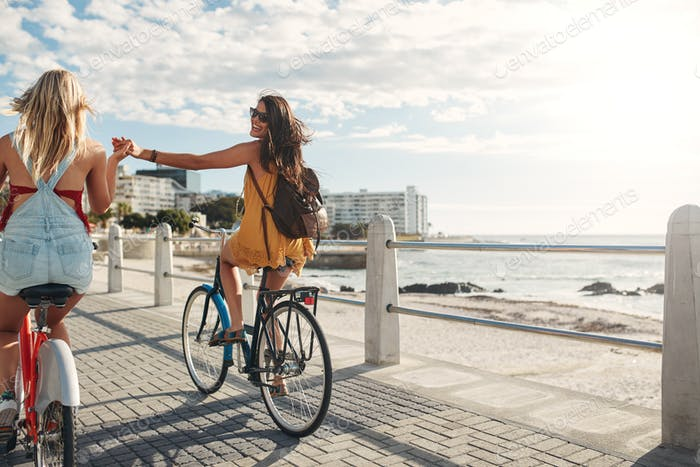 Two friends out for a bike ride by the sea