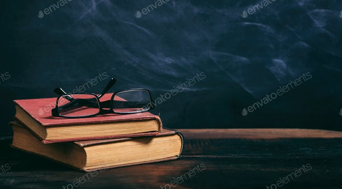 Old books and eye glasses on blackboard background