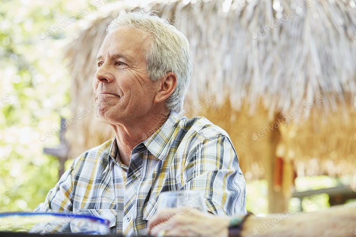 Smiling senior man with grey hair sitting outdoors.