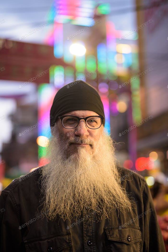 Mature bearded tourist man with eyeglasses in Chinatown at night