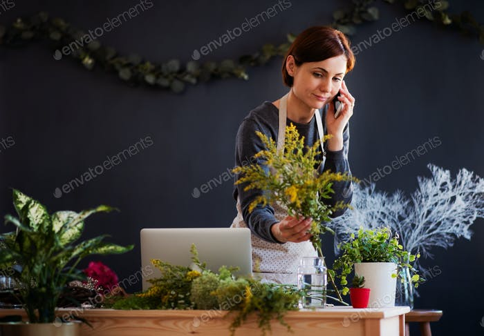 Young creative woman in a flower shop, using smartphone. A startup of florist business.