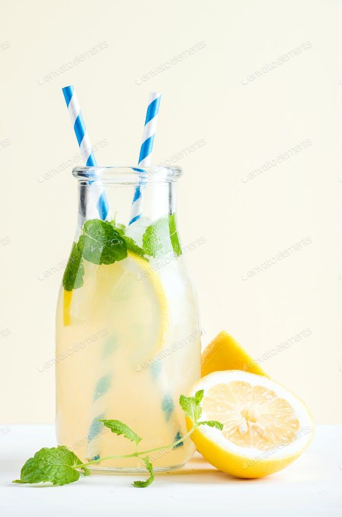 Bottle of homemade lemonade with mint, ice, lemons, paper straws and pastel blue background