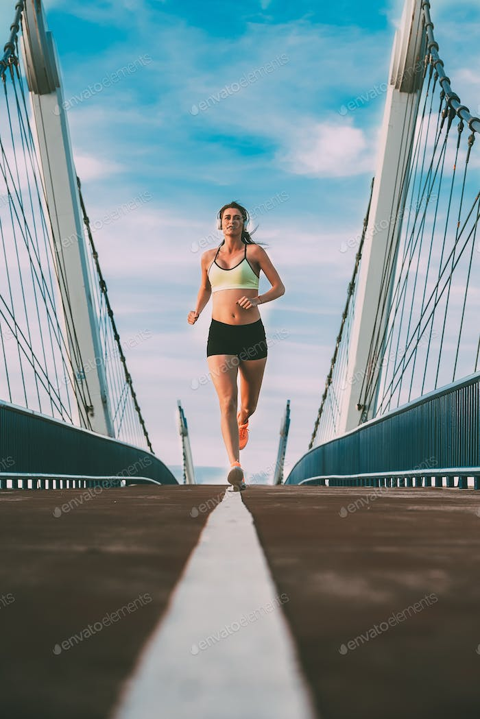 Young fit blonde woman running on the bridge