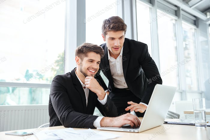 Two cheerful young businessmen using laptop on business meeting together